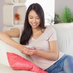 Pretty asian girl using her smartphone on the couch at home in t